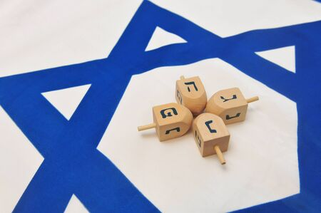 A white and blue Israeli Flag with the star of david on it with wooden dreidels for the Jewish holiday of Hanukkah. photo