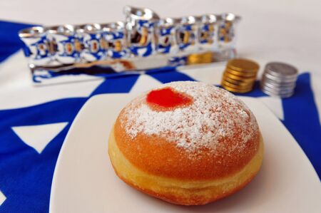 menora: Photo of a white and blue Israeli flag with the star of david with chocolate coins, sufganiya and silver menora - objects for the Jewish holiday of Hanukkah.