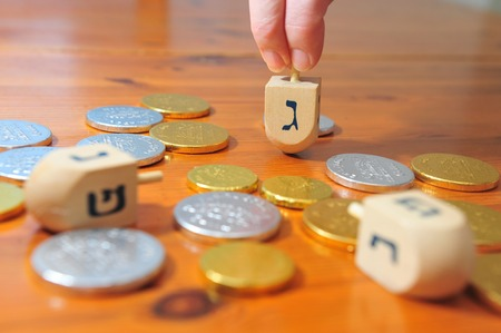 dreidel: Photo of someone spinning a spinning top (dreidel) and gelt (candy coins) for Hanukkah
