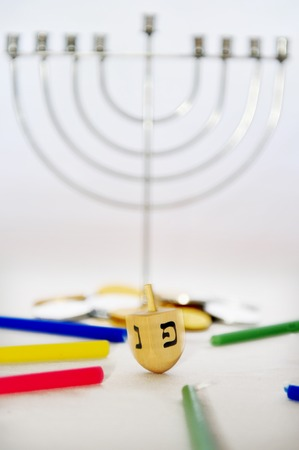 dreidel: Photo of a dreidel (spinning top), gelts (candy coins), a silver menorah and colorful candles for Hanukkah, isolated on white