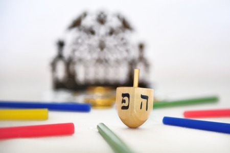 dreidel: Photo of a dreidel (spinning top), a bronze menorah, and colorful candles isolated on white - objects for the Jewish holiday of Hanukkah