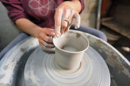 Female hands making pottery on spinning wheel photo