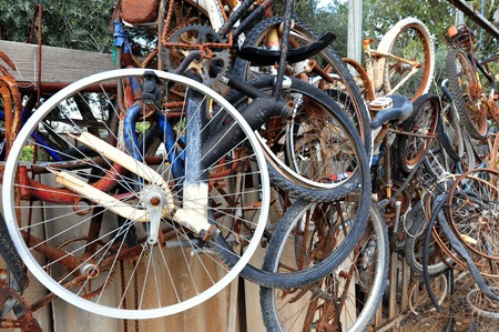 Old rusting bicycles and wheels in a junk yard.