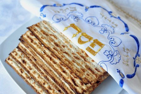 matzes: Traditional Jewish Matzo sheet on a Passover Seder table. Passover  is a predominantly Jewish holy day and festival. It commemorates the story of the Exodus, in which the ancient Israelites were freed from slavery in Egypt. Passover begins on the 15th day Stock Photo
