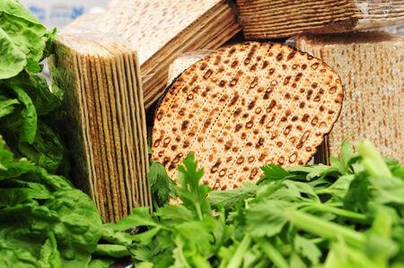 Une variété de différents types de matza (pain sans levain) entouré par les légumes verts comme la laitue et le céleri - alimentaire traditionnel utilisé pour les bénédictions sur le religieux fête juive de la Pâque de vacances (Pessah).