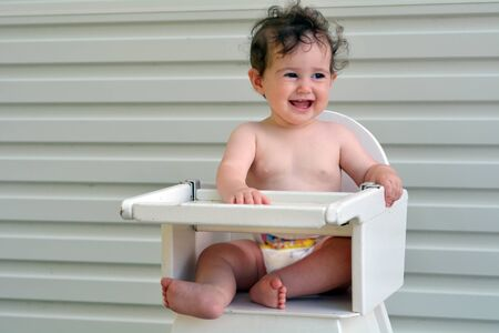 high chair: Smiley baby girl (age 8 months) sit on high chair.