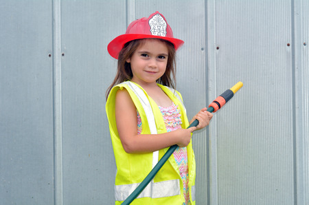 space age: Child (girl age 05) is posing on camera in fireman costume. concept photo copy space