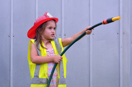 Child (girl age 05) is posing on camera in fireman costume. concept photo copy space