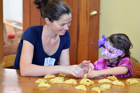 jewish home: Jewish Mother and her child (daughter girl age 5) in costume preparing and cooking togather home made Hamantaschen cookie  on Purim Jewish Holiday.