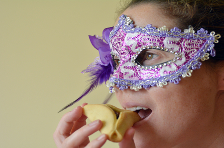 hamantash: Young Woman eat Hamantaschen cookie and wearing Purim jewish holiday carnival mask. Holiday concept. copy space Stock Photo
