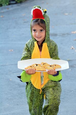 age 5: Jewish child (girl age 5) in alligator costume carry Mishloach Manot of oznei haman, hamantaschen, haman ears on Purim Jewish Holiday.