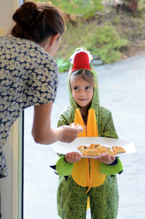 age 5: Jewish child (girl age 5) in alligator costume give Mishloach Manot of oznei haman, hamantaschen, haman ears to A jewish woman on Purim Jewish Holiday. Stock Photo