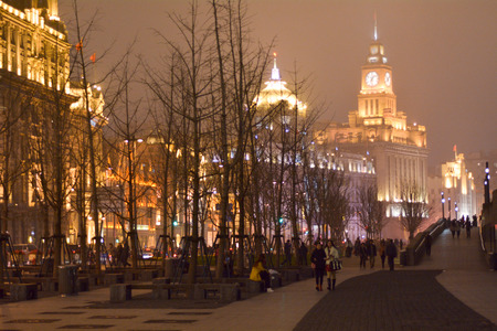 dozens: SHANGHAI, CN - MAR 16 2015:Visitors on Shanghai - The Bund or Waitan on foggy night.Shanghai Bund has dozens of historical buildings and It is one of the most famous tourist destinations in Shanghai.