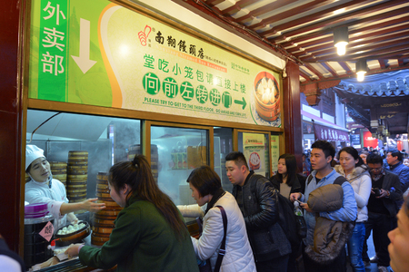 mart: SHANGHAI, CN - MAR 17 2015:Chines lines up to buy Dim sum dumplings food at Yuyuan Tourist Mart in Shanghai, China.Dim sum dumplings its the most popular and famous food in Shanghai, China