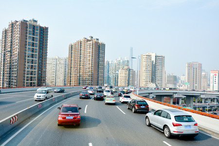 shanghai: SHANGHAI, CN - MAR 15 2015:Traffic against Shanghai cityscape.Shanghai is the largest Chinese city by population and the largest city proper by population in the world with over 2 million vehicles.