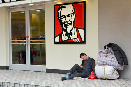 SHANGHAI, CN - MAR 15 2015:Chinese homeless on sit outside KFC fast food restaurant in Shanghai,China.More than 135 million people in China live on less than $1 a day