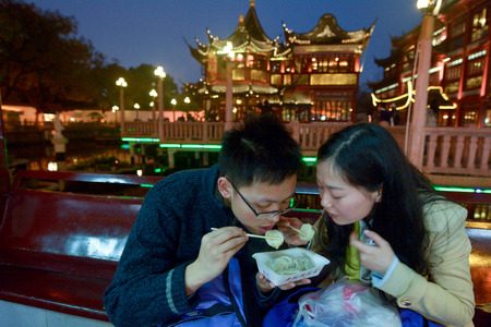 retailing: SHANGHAI, CN - MAR 16 2015:Chines couple eats dumpling in Yuyuan Tourist Mart in Shanghai, China.Shanghai Yuyuan Tourist Mart Company Limited, or Yuyuan Tourist Mart, is the largest retailing conglomerate in China.
