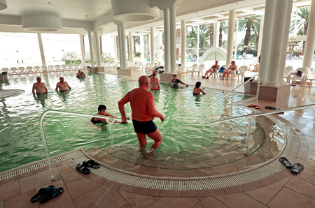holyland: EIN BOKEK, ISR - APR 30 2015:Visitors in Ein Bokek resort at the Sead Sea, Israel.As the place is rich in sulphur, the water is believed to be beneficial to treatment of diseases and allergies.