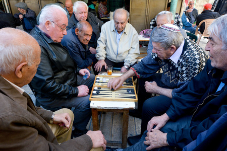 elderly: JERUSALEM - MAR 25 2015:Elderly men play backgammon in Mahane Yehuda Market in Jerusalem, Israel. Backgammon is among the oldest known board games, and many variants are played throughout the world.