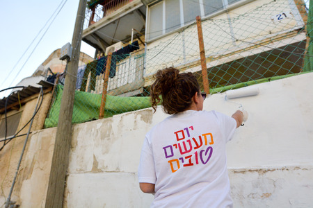deeds: JERUSALEM - MAR 25 2015:Israeli volunteer paint a wall in poor neighborhood in Jerusalem,Israel on Good Deeds Day. In 2015 930,000 participants from 61 countries took part in 11,000 projects worldwide Editorial