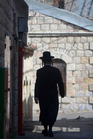 jewish community: JERUSALEM, ISR - MAR 19 2015:Orthodox Jewish man walks in old street in Jerusalem, Israel.About 30 percent of the Jewish population of Jerusalem are Orthodox Jewish people.