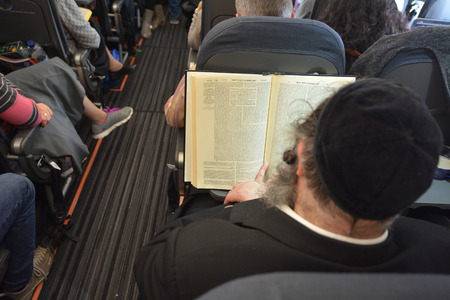 obligated: LONDON - MAR 20 2015: Orthodox Jewish men pray on a airplane during flight.Jewish men are obligated to pray three times a day within specific time ranges