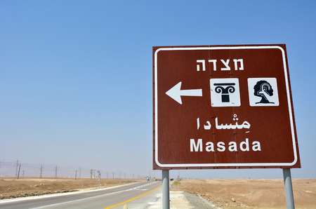 judaean desert: MASADA, ISR - APR 29 2015:Road sign to Masada stronghold in the Judaean Desert, Israel.Masada is one of Israels most popular tourist attractions Editorial