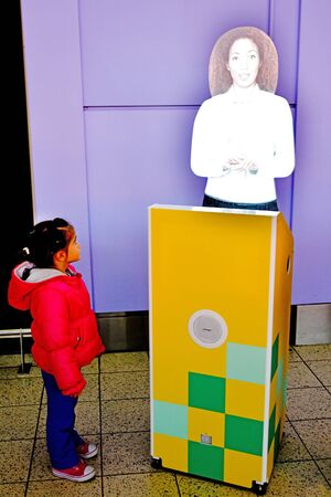 laser lights: LONDON - MAR 19 2015:Little girl (Talaya Ben-Ari age 05) get instructions from a 3D Woman hologram in London Luton Airport.Holograms are three-dimensional photographic images made with laser lights.