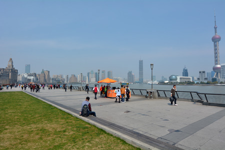 historical buildings: SHANGHAI, CN - MAR 17 2015:Visitors on Shanghai - The Bund or Waitan.Shanghai Bund has dozens of historical buildings and It is one of the most famous tourist destinations in Shanghai.
