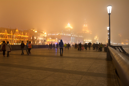 historical buildings: SHANGHAI, CN - MAR 16 2015:Visitors on Shanghai - The Bund or Waitan on foggy night.Shanghai Bund has dozens of historical buildings and It is one of the most famous tourist destinations in Shanghai.