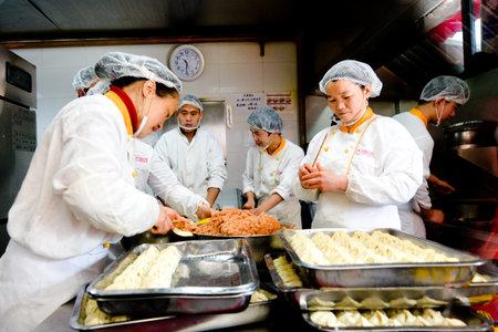 mart: SHANGHAI, CN - MAR 17 2015:Chines chefs prepare Dim sum dumplings food at Yuyuan Tourist Mart in Shanghai, China.Dim sum dumplings its the most popular and famous food in Shanghai, China
