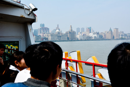 dozens: SHANGHAI, CN - MAR 17 2015:Ferry passengers loooks at  Shanghai - The Bund or Waitan. Shanghai Bund has dozens of historical buildings and It is one of the most famous tourist destinations in Shanghai.