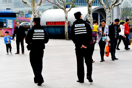 convicted: SHANGHAI - MAR 17 2015:Chinese police offices guarding Nanjing Road in Shanghai, China.Since 2001, over 7,000 Chinese convicted on terrorism charges mainly Tibetan and Muslim Uyghur ethnic groups