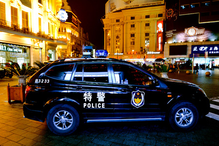 convicted: SHANGHAI - MAR 17 2015:Chinese police car guarding Nanjing Road in Shanghai, China.Since 2001, over 7,000 Chinese citizens convicted on terrorism charges mainly Tibetan and Muslim Uyghur ethnic groups