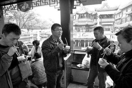 mart: SHANGHAI, CN - MAR 17 2015:Chines people eats Dim sum dumplings food at Yuyuan Tourist Mart in Shanghai, China.Dim sum dumplings its the most popular and famous food in Shanghai, China