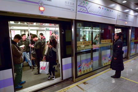 ch: SHANGHAI, CH - MAR 25 2015:Passengers in Shanghai Metro train station. Shanghai Metro ranks third in the world in annual ridership, with 2.5 billion rides delivered in 2013. Editorial