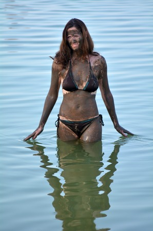 sourced: A young woman in a bathing suit is enjoying the natural mineral mud sourced from the Dead Sea  Israel. Stock Photo