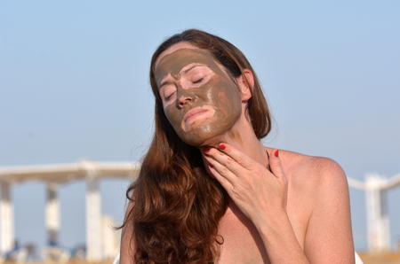 sourced: Young woman applying natural mineral mud on her face sourced from the Dead Sea Israel Stock Photo
