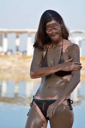 sourced: Woman applying natural mineral mud on her body, sourced from the Dead Sea Israel Stock Photo