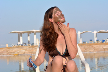mud woman: Young woman applying natural mineral mud on her face, sourced from the Dead Sea Israel Stock Photo