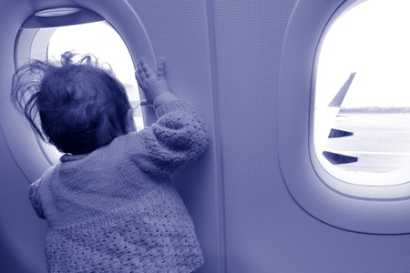 air baby: Baby girl looks out from airplane window during air travel. concept photo copy space (BW)
