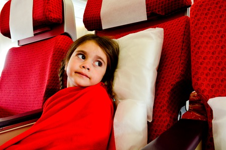 phobia: Little girl with a flying phobia in a plane scared to fly during air travel flight. Stock Photo