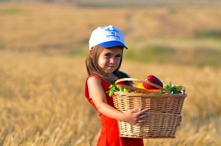 ユダヤ教の祝日、イスラエルのシャブオット中最初のフルーツのバスケットとほとんどユダヤ人イスラエルの少女。 写真素材