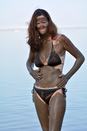 sourced: Woman applying natural mineral mud on her body sourced from the Dead Sea Israel