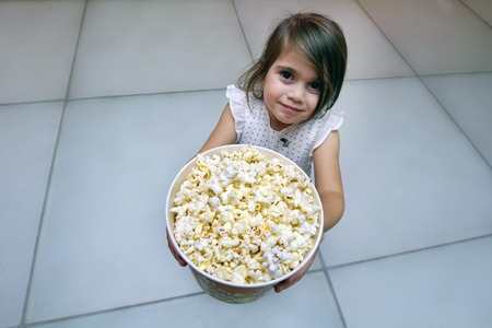 age 5: Little child girl age 5 eats popcorn. Concept photo of children health care healthy food and diet Stock Photo