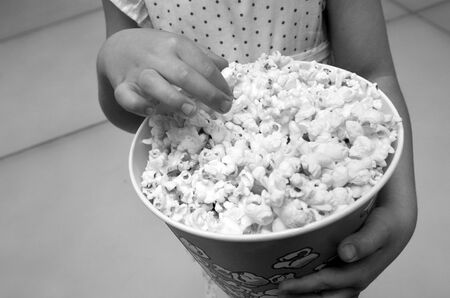 age 5: Hands of a little child girl age 5 eats popcorn. Concept photo of children health care healthy food and diet