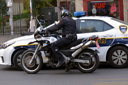 motorcycle police officer: TEL AVIV, ISR - MAR 27 2015:Israel Police officer on a motorbike and a patrol car.The Israel Police are a professional force, with some 35,000 persons on the payroll.