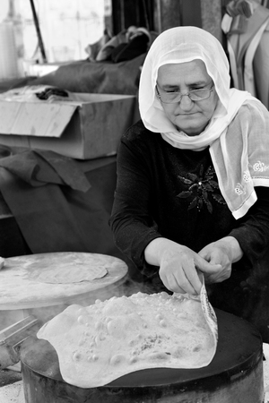 middle eastern woman: TEL AVIV, ISR - APR 06 2015:Druze woman prepare Taboon bread in the Carmel market in Tel Aviv, Israel.Taboon bread is a staple of Middle Eastern cuisine worldwide.