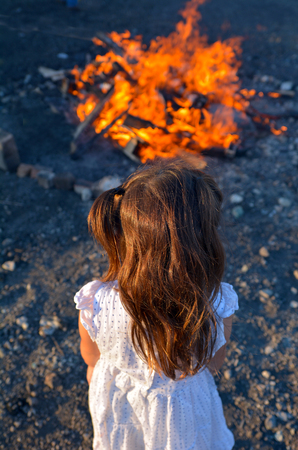 lag: Little Jewish girl stand beside bonfire celebrate  Lag BaOmer Jewish Holiday.