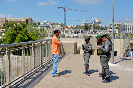 border patrol: JERUSALEM - MAY 05 2015:Israeli border patrol policewomen checking Arab man ID and work permits.The force securing Israel borders and assisting IDF and law enforcements in the West Bank and Jerusalem.